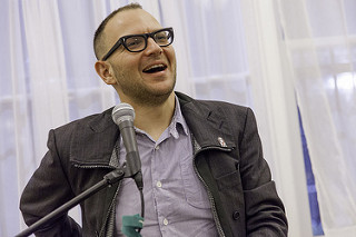 [ A photo of Cory Doctorow. He is giving a talk in front of white curtains. He is wearing a dark jacket and light blue shirt. ]