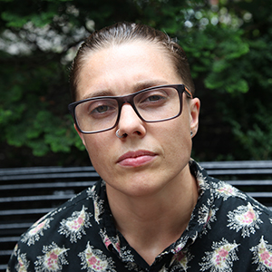 [ A photo of Kade Crockford. They are sitting on a bench in front of some trees, wearing a black shirt with pink and white designs. ]