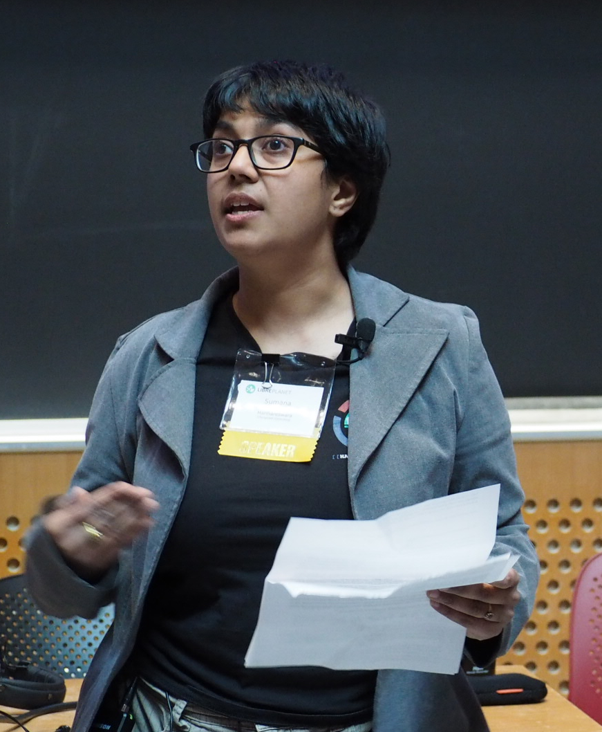 [ A photo of Sumana Harihareswara. She is standing in front of a black board, delivering a talk. She is wearing a black shirt and a grey blazer. ]