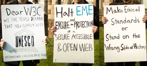 Three protest signs against DRM.