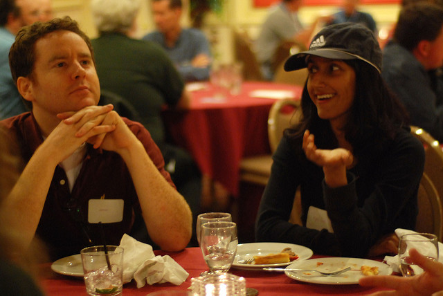 A woman (on the right) and a man (on the left) sitting at a table in a banuet hall. They are both wearing black shirts. The woman is speaking, with a smile and a hand gesturing forward while the man is looking off into the distance, a thoughtful look on his face.