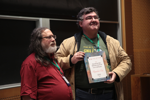 Richard Stallman stands on the left. He is wearing a red polo shirt. He has long grey hair and a long, grey beard. Alexandre Oliva stands to his right. He is holding a Free Software Award--a plaque. He is wearing a green shirt, a tan jacket, and glasses. They both look very happy.