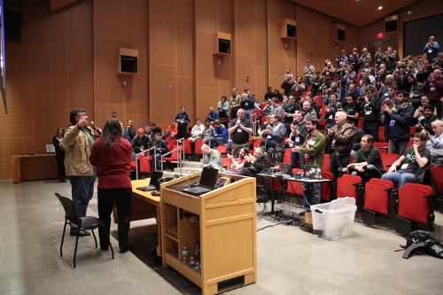 Alexandre Oliva and Richard Stallman stand in the front of a lecture hall, facing away from the camera. The hall is full of people, and they are standing in front of their seats and clapping.