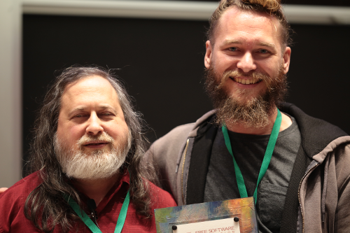 Richard M. Stallman stands to the left of the photo. He has long grey hair and a grey beard. He is wearing a red polo shirt, and a green lanyard with a LibrePlanet conference badge. Conor Schaefer stands to the right. He is taller than Richard. His hair is dirty blond--and tied into a bun. His beard is brown and grey. He is wearing a grey shirt, a grey hoodie, and a green lanyard. He is holding a Free Software Award.
