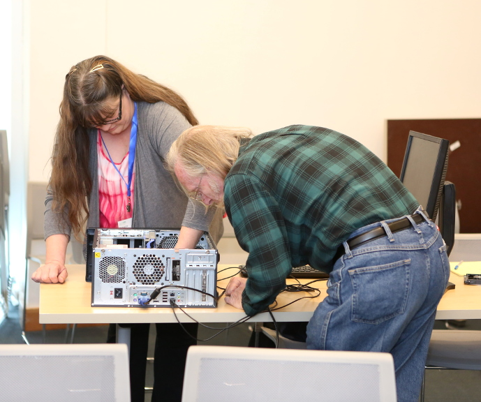 a man and woman tinkering with a desktop computer.
