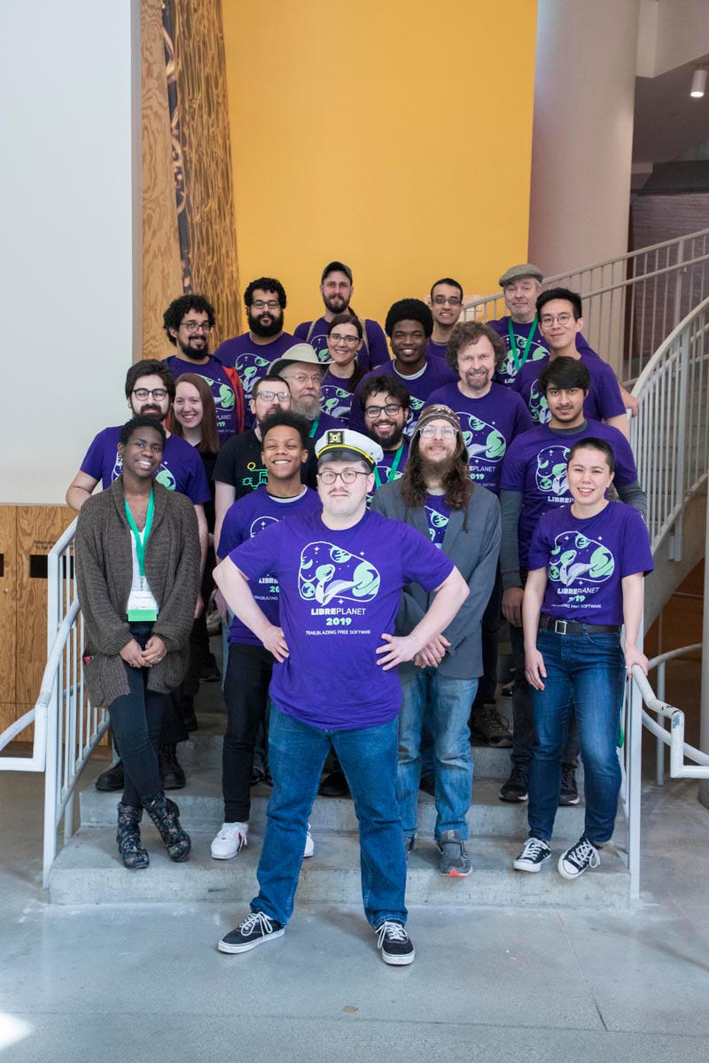LibrePlanet volunteer captain Matt Lavallee posed in front of a staircase with a large group of LibrePlanet volunteers in matching purple LibrePlanet shirts