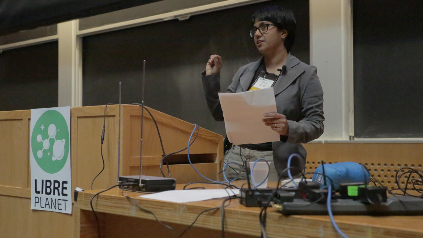 [ Sumana Harihareswara speaking at a podium at LibrePlanet 2016. Between her and the camera is a table strewn with cables and computer equipment. ]