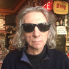 [ A man in dark glasses in a pub. ]