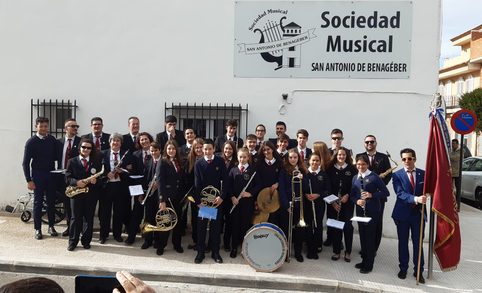 Students and teachers of the Sociedad Musical de San Antonio de Benagéber, a music school in Spain, pose with their instruments and flags.