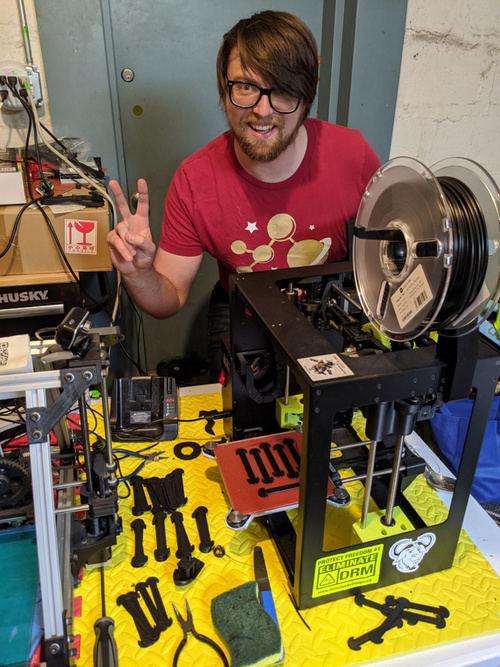 FSF Web Developer Michael McMahon poses with the 3D printers in his garage that are being used to manufacture protective gear and medical supplies in the HACKERS and HOSPITALS initiative.